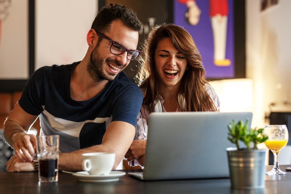 Zwei junge Menschen sitzen lächelnd vor einem Notebook