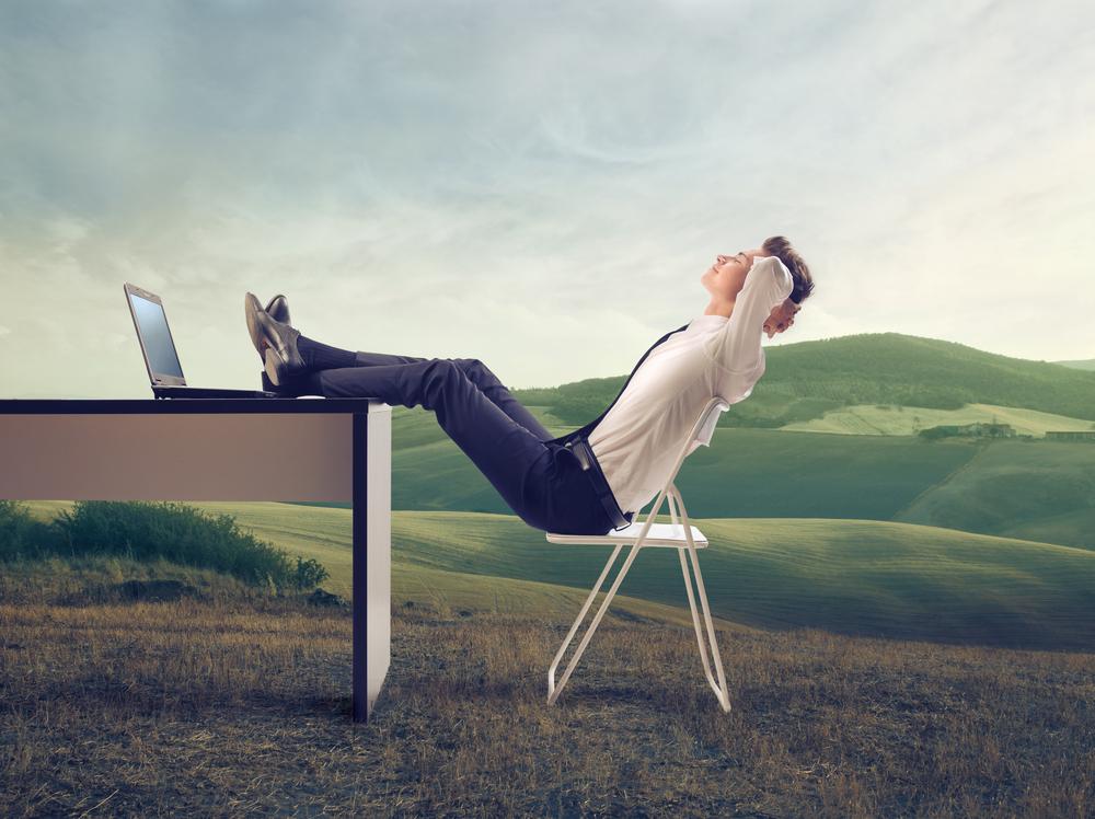 Ein junger Mann sitzt mit dem Notebook auf einer Wiese. Im Hintergrund sind Berge zu sehen.