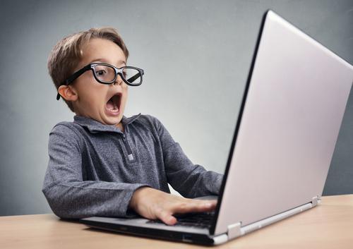 Ein junge mit Brille sitzt vor einem geöffneten Notebook